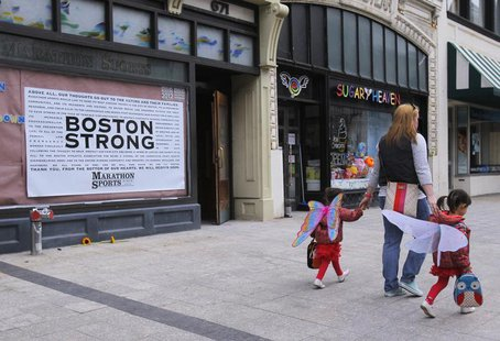 A woman walks her children wearing wings in front of the site of the first explosion on Boylston Street after the street reopened to the pub