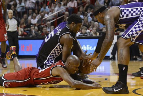 Miami Heat's Ray Allen (L) scrambles for a loose ball with Sacramento Kings' John Salmons (C) and DeMarcus Cousins (R) during the first half