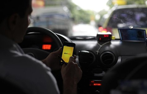 A taxi driver checks an app on his smartphone in Rio de Janeiro April 15, 2013. REUTERS/Ricardo Moraes