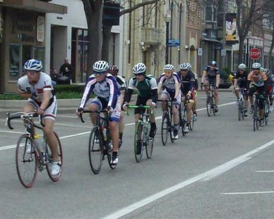 Cyclists sprint along 8th Street in downtown Holland during the first Queen's Criterium race on Apr. 28, 2013.