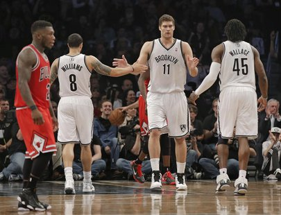 Brooklyn Nets guard Deron Williams (8), center Brook Lopez (11) and forward Gerald Wallace (45) tap hands as Chicago Bulls point guard Nate