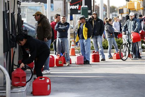 People stand in line with gas cans to fill at one of the few gas stations open on hard-hit Staten Island in New York City following Hurrican