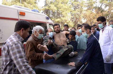 Residents and medics transport a Syrian Army soldier, wounded in what they said was a chemical weapon attack near Aleppo, to a hospital Marc