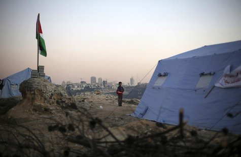 A boy stands near a Palestinian flag placed near newly-erected tents in the West Bank village of Beit Iksa, between Ramallah and Jerusalem J