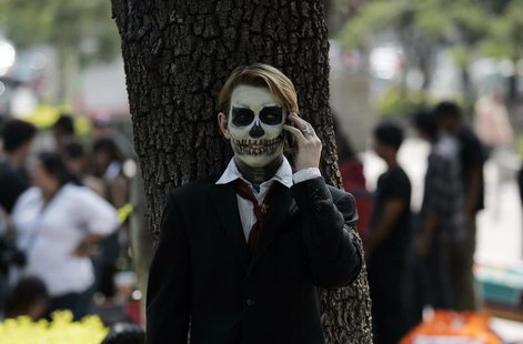 A fine arts student wears make-up as he talks on the phone during the Catrina's parade in Guadalajara October 26, 2012. REUTERS/Alejandro Ac