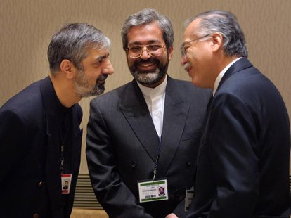 Chairman of the Group of 77, Ambassador Bagher Asadi, (L) and Mohsen Nourbakhsh, Governor of the IMF for Iran (C), talk with outgoing Chairm