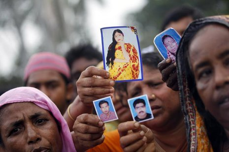 Relative show pictures of garment workers who are missing, during a protest to demand capital punishment for those responsible for the colla