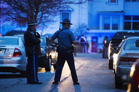 Law enforcement officials stand at the scene on Franklin St. as the search for Dzhokhar Tsarnaev, the surviving suspect in the Boston Marath