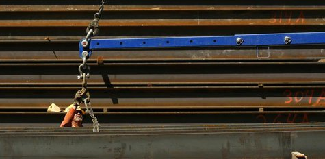 A worker guides a steel beam into place at a construction site in San Francisco, California September 1, 2011. REUTERS/Robert Galbraith