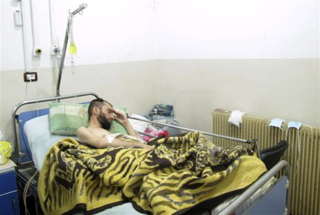 A wounded Syrian refugee who activists said was injured during shelling by forces loyal to Syrian President Bashar al-Assad, lies in a hospi