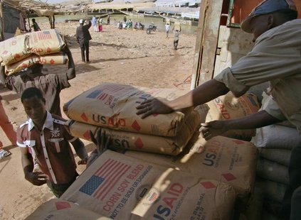 Men transport humanitarian food aid onto pirogues at Mopti February 4, 2013. REUTERS/Alain Amontchi