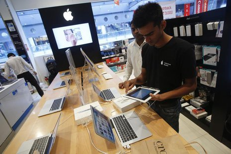 A salesperson unpacks an Apple iPad Mini to test it for a customer in the Apple specialty section of a Croma retail store in Mumbai February