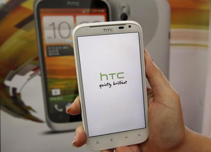 A salesperson shows an HTC Sensation XL smartphone in a mobile phone shop in Taipei April 8, 2013. REUTERS/Pichi Chuang