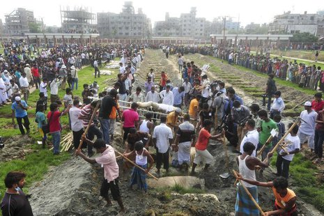 Workers dig mass graves during a mass burial of unidentified garment workers, who died in the collapse of the Rana Plaza building in Savar,