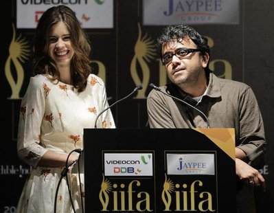 Bollywood actress Kalki Koechlin smiles as director Dibakar Banerjee (R) speaks during the opening news conference of the 13th International