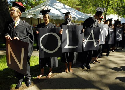 "Students hold letters spelling out ""No layoffs"" during the 361st Commencement Exercises at Harvard University in Cambridge, Massachusetts Ma"
