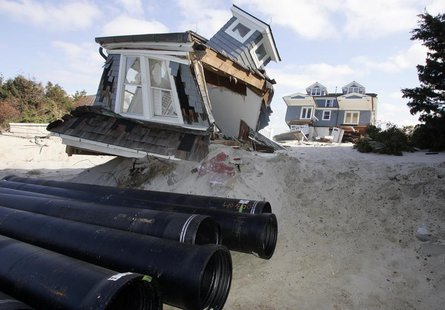 Sewer line pipes waiting for installation are stacked near parts of a house that broke off and washed up near the street in Mantoloking, New