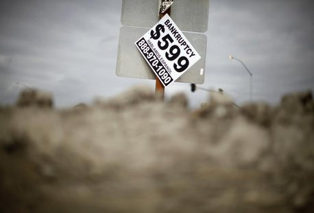 A sign advertising bankruptcy filing is seen hanging off a road sign in San Bernardino, California September 11, 2012. REUTERS/Lucy Nicholso