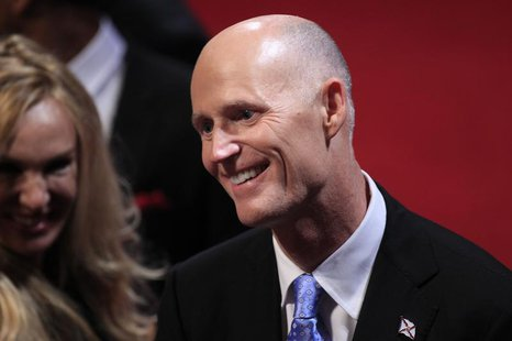 Florida Governor Rick Scott greets an attendee in the audience before the start of the final U.S. presidential debate in Boca Raton, Florida