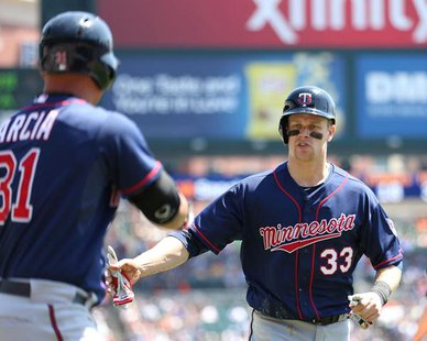 Minnesota 1B Justin Morneau (R) is congratulated by LF Oswaldo Arcia (L) after scoring in the first inning of the Twins' 6-2 win over the Detroit Tigers at Comerica Park in Detroit on May 1, 2013. (photo courtesy Minnesota Twins)