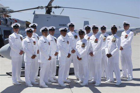 Members of first U.S. Navy helicopter squadron to include manned and unmanned aircraft pose with one of their aircraft after a ceremony at N