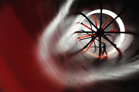 A worker walks past newly-made cement mill barrels at a heavy equipment manufacturing factory in Luoyang, Henan province May 1, 2013. REUTER