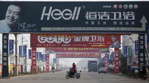 A motorist drives under advertisement boards at the business area of Ruzhou county, China's central Henan province, December 18, 2012. REUTE