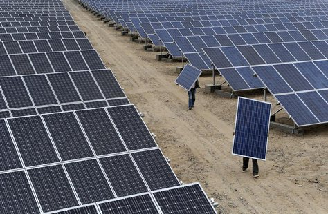 Employees carry solar panels at a solar power plant in Aksu, Xinjiang Uyghur Autonomous Region May 18, 2012. REUTERS/Stringer