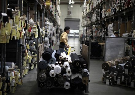 A worker wheels rolls of cloth through the Karen Kane clothing company in Los Angeles, California June 30, 2011. REUTERS/Lucy Nicholson