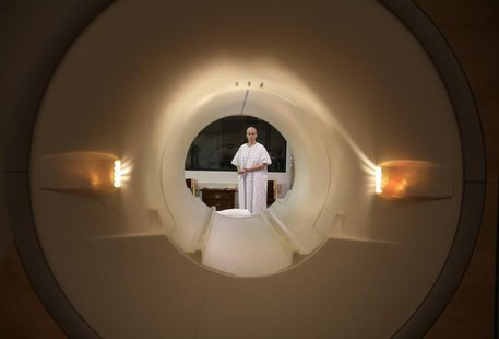 A cancer patient is seen through the tube of a magnetic resonance imaging scanner as she prepares to enter the MRI machine for an examinatio