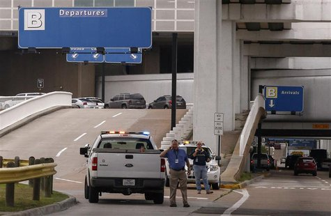 Airport security officials block vehicle access to Terminal B after a gunman opened fire at the terminal in George Bush Intercontinental Air
