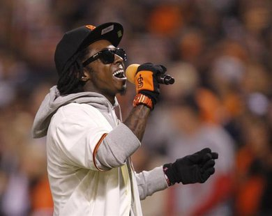 "Rapper Lil Wayne sings ""Take Me Out To The Ball Game"" during the seventh inning stretch in Game 6 of the MLB NLCS playoff baseball series be"