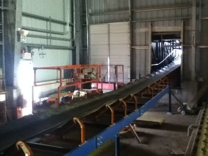 This conveyor belt leaves the storage building and transports biomass fuel to the boiler.