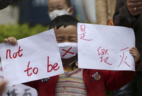 A boy wearing a mask holds papers as he protests against a planned refinery which produces the chemical paraxylene (PX), at a square in Kunm