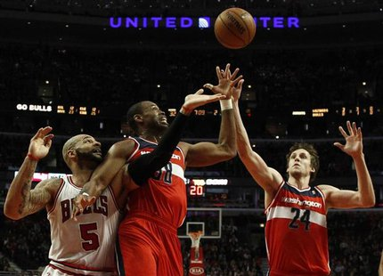 Washington Wizards' Jason Collins (C) and Wizards' Jan Vesely (R) battle for a rebound against Chicago Bulls' Carlos Boozer during the first
