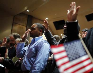 Over 90 immigrants representing over 40 countries take the oath of citizenship during a naturalization ceremony to become new citizens of th