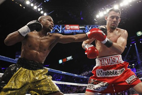 WBC welterweight champion Floyd Mayweather Jr. (L) of the U.S. connects a punch on Robert Guerrero, also of the U.S., during their title fig