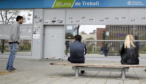 "People wait for an employment office to open in Badalona, near Barcelona, April 25, 2013. The stickers on the wall read, ""Unemployment"". REU"