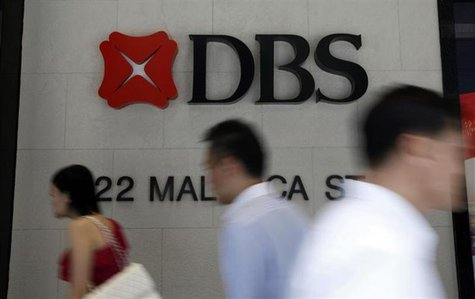 Office workers pass a logo of Development Bank of Singapore (DBS) in the central business district in Singapore April 30, 2013. REUTERS/Edga
