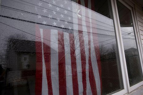 An American flag is seen through the window of a destroyed and abandoned home after Hurricane Sandy on Tarlton Street in the Oakwood Beach s
