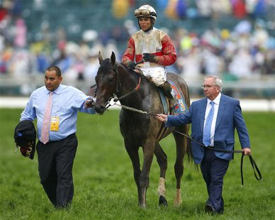 Orb trainer Claude McGaughey (R) walks his horse, with Jockey Joel Rosario aboard, to the winner's circle after the running of the 139th Ken