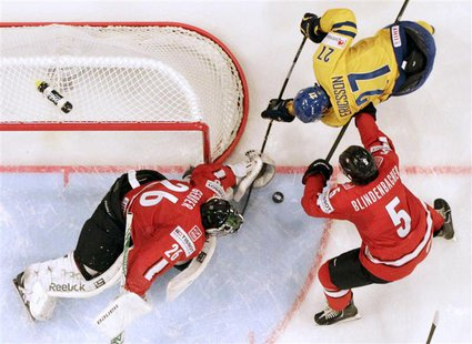 Switzerland's goalie Martin Gerber (L) and Severin Blindenbacher (R) fight for the puck with Sweden's Jimmie Ericsson during their 2013 IIHF