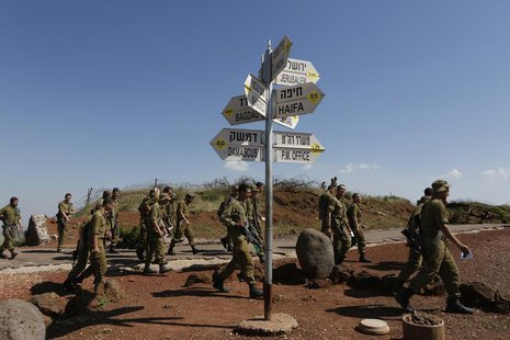 Israeli soldiers walk past signs pointing out distances to different cities at an observation point on Mount Bental in the Israeli-occupied