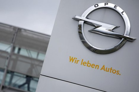 A sign depicting the Opel logo is pictured in front of the Opel Adam AG headquarters as a person passes by in Ruesselheim April 10, 2013. Th