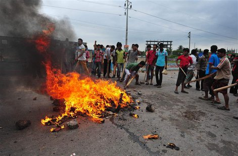 Activists of Hefajat-e Islam set fire to tyres and pieces of wood as they block a street during a clash with the police in Narayanganj May 6