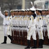 Members of the People's Liberation Army's navy guard of honour prepare to use a string to ensure that soldiers stand in a straight line befo