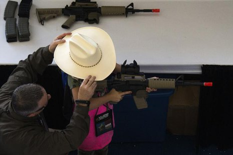 A man adjusts a girl's hat before she takes aim with an airsoft gun during the NRA Youth Day at the National Rifle Association's annual meet