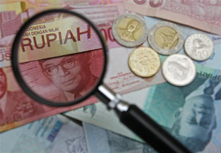 A 100,000 Indonesian rupiah note is seen through a magnifying glass among other Southeast Asian currencies in this photo illustration taken