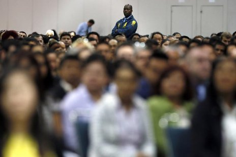 A security guard stands guard near immigrants during a naturalization ceremony in Los Angeles April 16, 2013. REUTERS/Lucy Nicholson