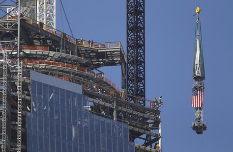 The final section of the spire that will top off One World Trade Center is raised past iron workers to the top of the building in New York,